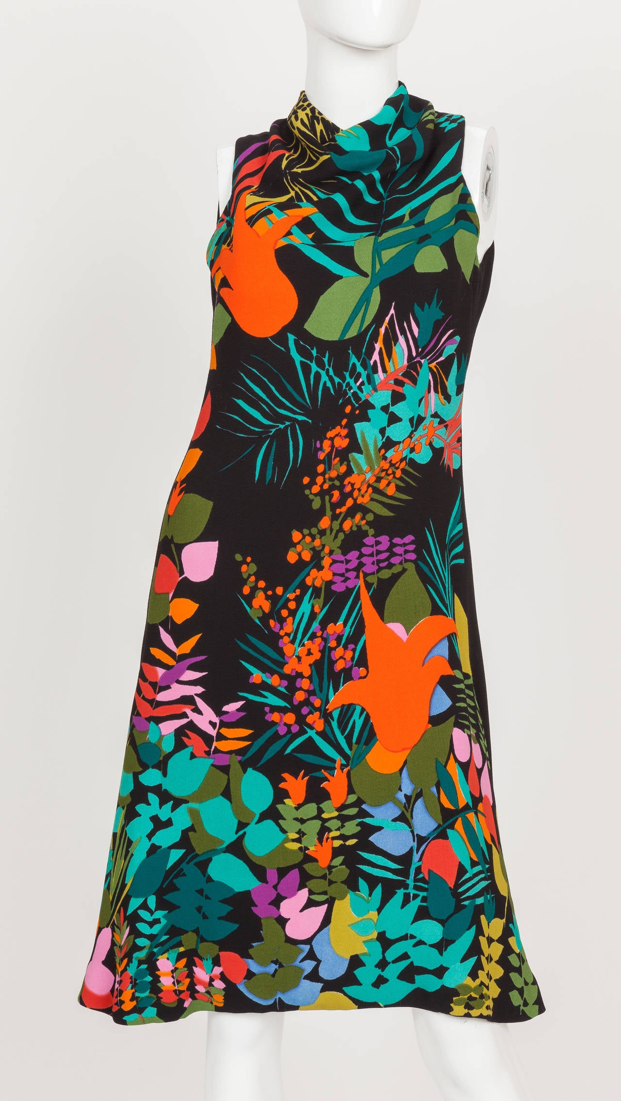 A Pauline Trigere sleeveless cocktail or day dress from the late 1970's, early 1980's featuring a floral print on black background with mini cowl-neckline. This A-line dress with flounced hem is lined with silk and has two small round weights built
