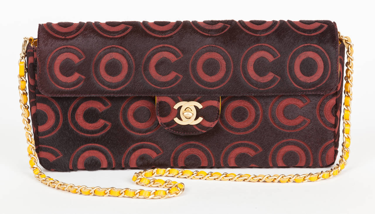 "A 100% authentic Chanel burgundy and black pony hair & leather handbag/clutch with the word ""COCO"" spelled throughout. Features brushed matte gold Chanel CC lock at the front, a golden/amber yellow leather-lined interior and a"