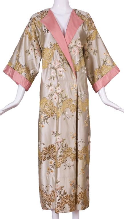 A circa 1960 Madame Gres haute couture kimono evening dress in pastel hues and a floral embroidered motif that includes gold thread. Trimmed at the neck, 3/4 sleeves and an attached waist tie with rose pink silk taffeta. The kimono can be worn with