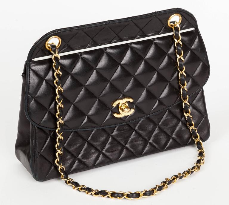 A 1991 Chanel quilted soft calfskin leather handbag with double chain shoulder strap, gold tone hardware, turn lock fastener and white leather trim both at front and back exterior pocket edge. Opens to one main compartment with side pocket. Stamped