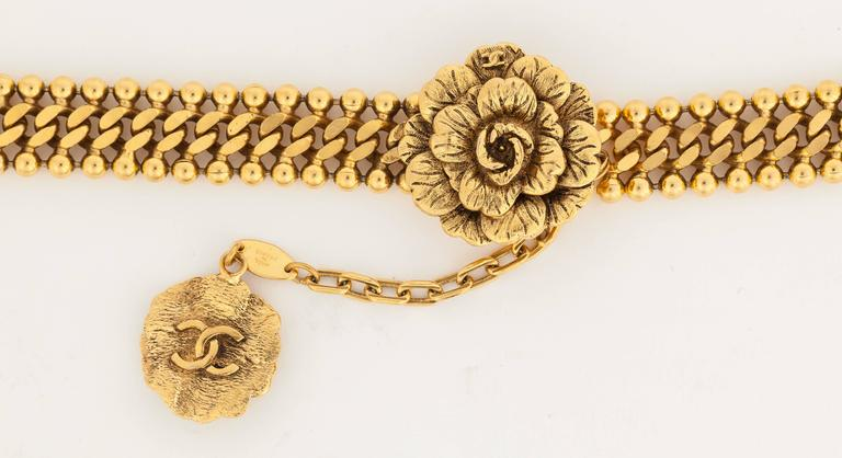 A 1983 Chanel gold tone metal chain belt with flower buckle and hook fastener. There is a flower charm with CC logo on the underside hanging off the chain that fastens to the buckle. In excellent condition. Stamped: Chanel