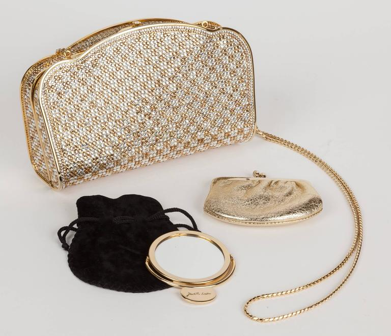 A circa 1990's Judith Leiber gold & silver/white bejeweled Swarovski crystal minaudière with gold tone metal envelope-shaped box form and curved/scalloped edges. Features a gold leather interior, gold chain shoulder strap, a bezel-set crystal push