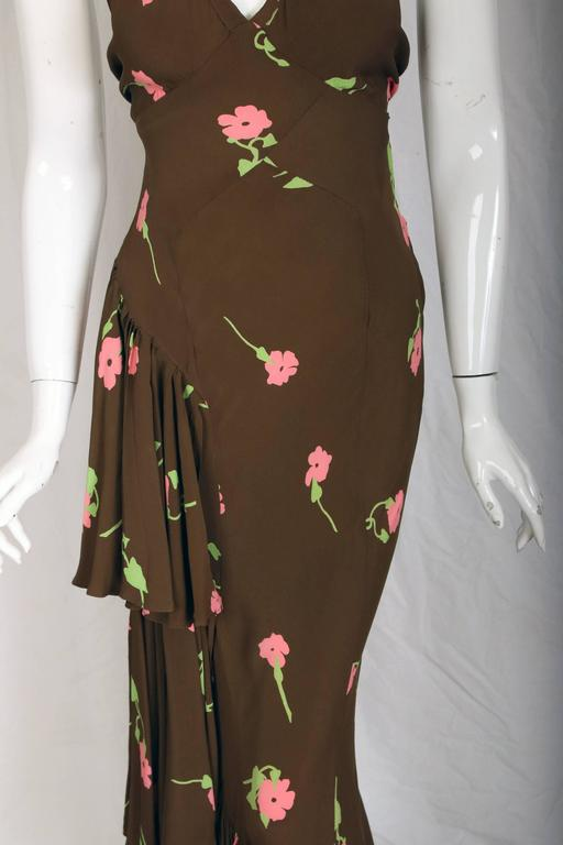 An Ossie Clark bias-cut evening gown with a Celia Birtwell floral print. Gown features one-sided ruffles down the right leg and a shoulder ruffle at the opposing, left shoulder. British Size tag 10 which would likely fit a US 2 or 4. The dress is in