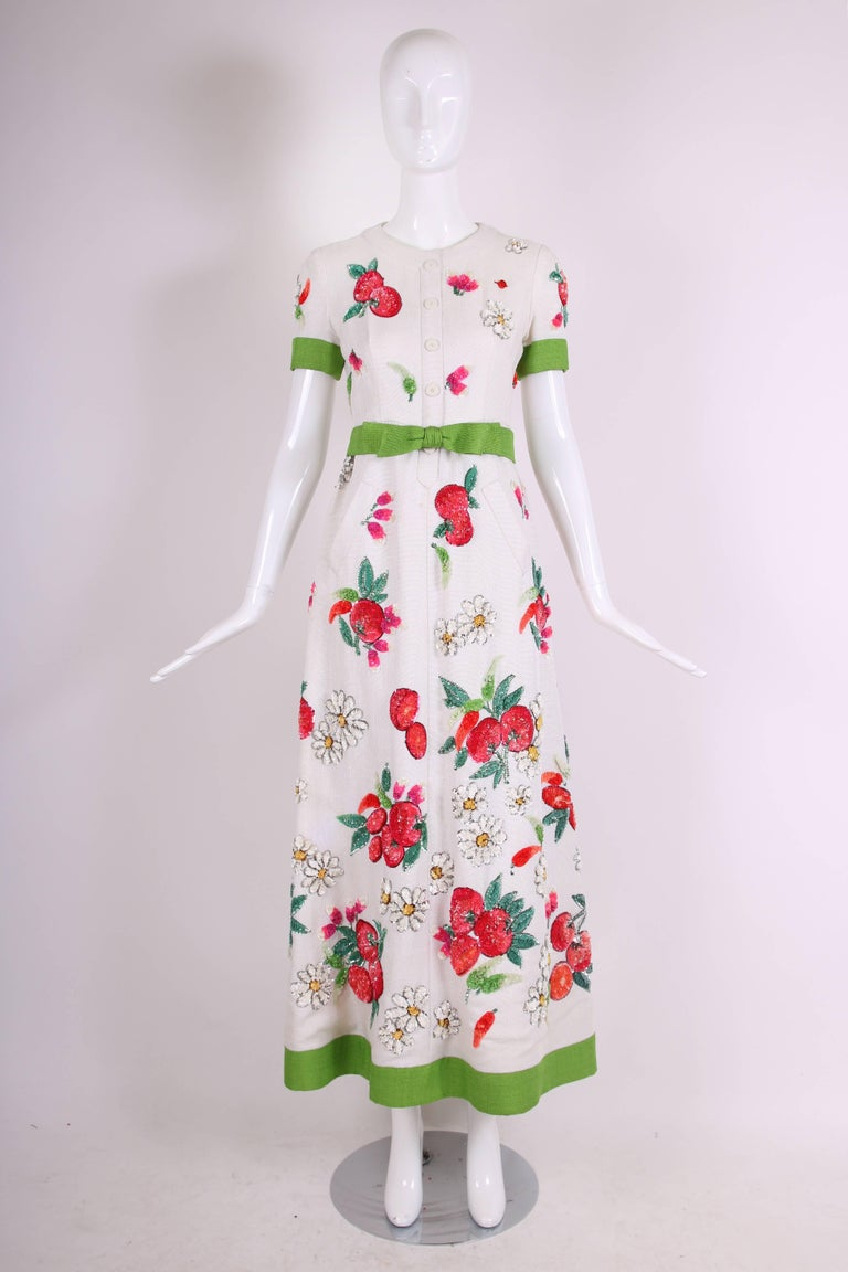 1960's Nina Ricci for Bergdorf Goodman heavy linen summer evening gown featuring clusters of sequined daisies and fruit. Entirely lined with silk taffeta and comes with a detachable green belt. In very good vintage condition with some missing