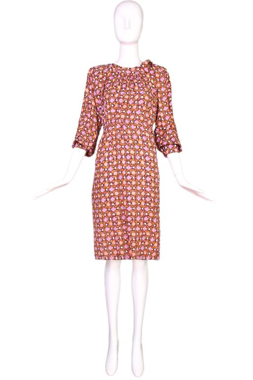 1984 Yves Saint Laurent silk day dress in orange, purple, and grey geometric print with long side neck ties and gold tone etched button closures down center left side. See original archival runway photographs in listing. In excellent condition. Size