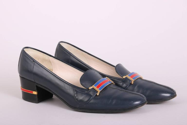 1970's Gucci navy leather heeled loafers with gold tone hardware and a red & blue enameled bar at the top. Leather is quite soft and In very good condition with some extremely light scuffs at the toe and wear at the bottom of the soles ***please