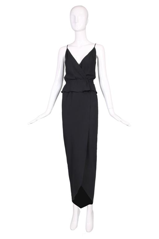 """1970's Halston black silk crepe 2-piece consisting of a low V-neck spaghetti strap top and tulip silhouette faux-wrap skirt. In excellent condition. Top: Bust - 34"""" Waist - 26"""" Skirt: Waist - 28"""" Hip - 38"""" Length - 48"""""""