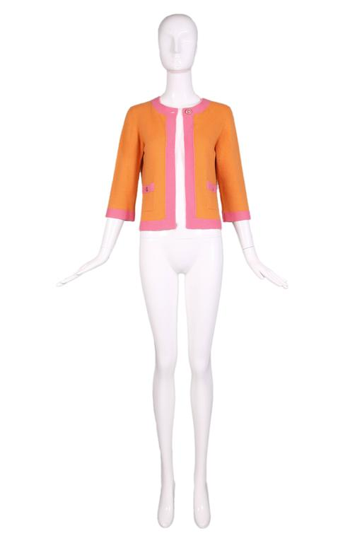 2007 P/E Chanel orange cashmere open front cardigan with pink trim. Features round pink & gold toned Chanel CC Logo buttons at top closure and at two front pockets. In excellent condition. Size EU 38.