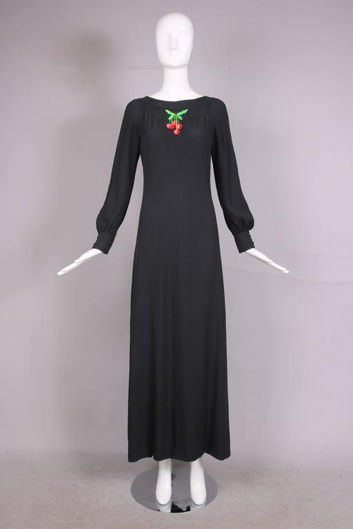 1970's Valentino A-line black crepe maxi dress with dramatic side slit. Features pin tucking detail at boat neck and an embroidered single cherry cluster applique. Cuffs each have a two black fabric-covered button closure. In excellent condition