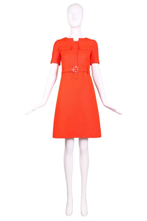 1970's Courreges haute couture orange wool short sleeved day dress with frontal snaps, two frontal decorative pocket flaps, two pockets hidden within the seams running down the skirt front, and belt at waist. In excellent condition. Size EU