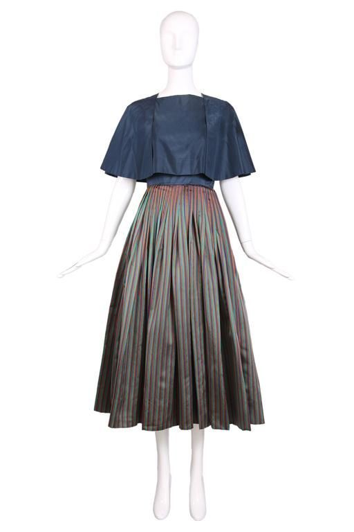 1983 Madame Gres blue taffeta cocktail dress with square neckline and thin spaghetti straps. The voluminous skirt has vertical stripes in blue, green, orange, and brown. Dress has a matching blue taffeta cropped cape with ties at back. In excellent