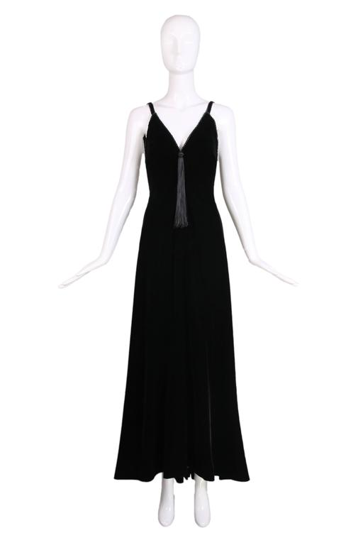 Stunning ca.1985 Givenchy haute couture black silk velvet evening gown with a V-neckline that features braided silk trim and a single tassel that hangs at the V. The gown has an open back that culminates in a V, also with a single tassel and there