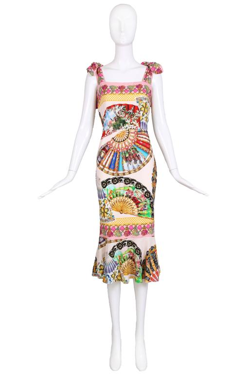 Dolce & Gabbana silk cocktail dress with shoulder straps that tie in bows, a square neckline and trumpet hem. Dress features a multi-colored graphic scenic print dominated by vintage hand fans, tassels, vignettes of Italy, lattice work and