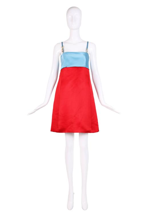 Vibrant crimson red and sky blue color block mini dress in duchess satin. The dress features a empire waist, spaghetti straps with rhinestone Versace & V embellishments on straps. Size tag 42.