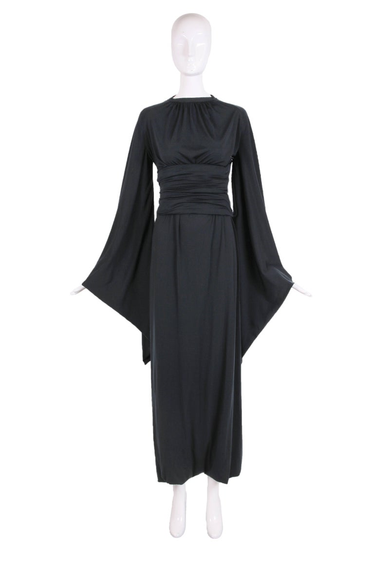 Ca.1977 Pierre Cardin black jersey harem dress with pagoda sleeves and attached belt. The dress is actually sewn closed at the hem with two openings for either leg. In excellent condition with some very tiny abrasions to the jersey fabric scattered