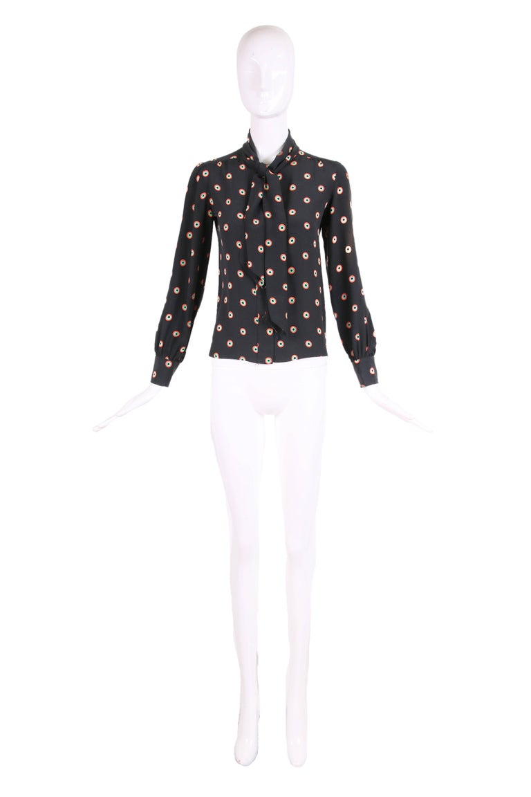 """1970's Yves Saint Laurent YSL black silk blouse with with green, red and black circle print and neck ties. Size 34. In very good condition with some light fading to the left arm. Please see measurements. MEASUREMENTS: Shoulders - 13.5"""" Sleeves"""