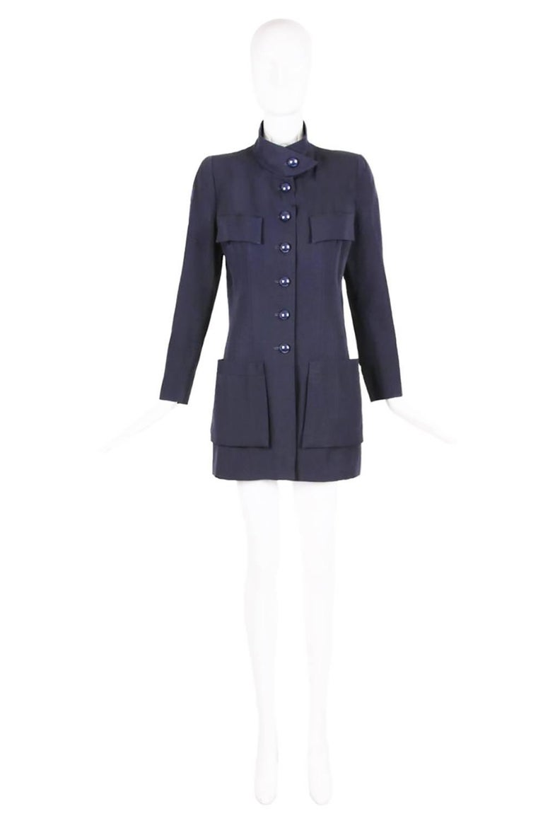 Chanel haute couture navy blue wool jacket with six oversized shiny button closures down center front and at the cuffs, two oversized frontal pockets at the hips, faux patch pockets at the chest and paneling design down the front and back. The