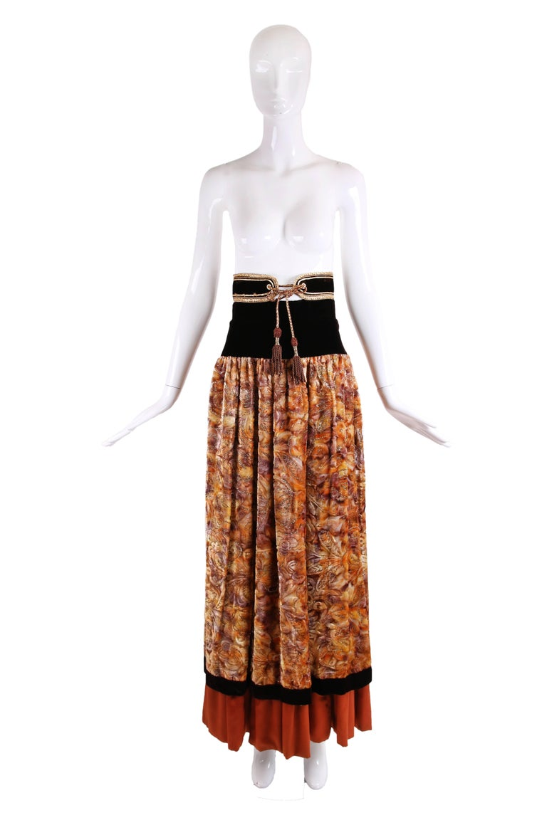 Inspired by Yves Saint Laurent but unlabeled velvet burnout maxi skirt with a velvet waist band, gold metallic cord trim and ties and a orange/brown layer of silk at the interior that peeks out at the hem. In very good condition - appears that the