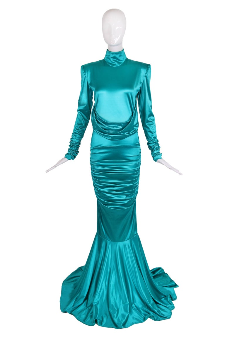 1988 Patrick Kelly turquoise stretch mermaid gown with high collar, crossed swags, ruching through the hips and trained circle skirt from the knee. In very good condition with some minor pulls, lipstick marks on swags and faint stain on train. No