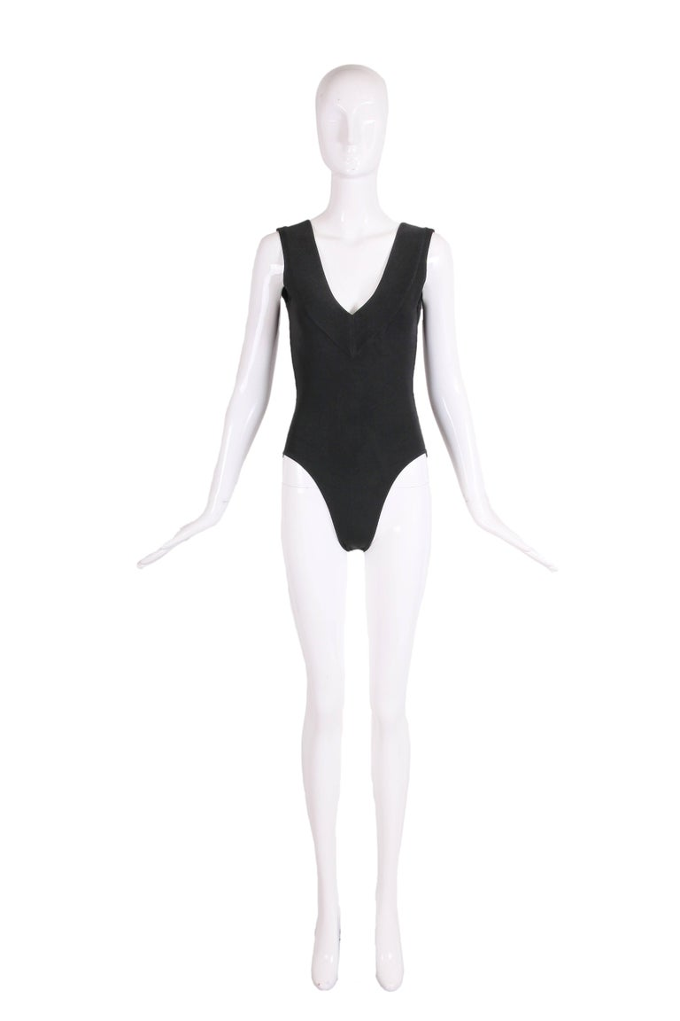 1990's Azzedine Alaia black stretch body suit with deep v-neckline at back and front. There are three snap closures at the bottom. In excellent condition - tag size Small - please consult measurements.