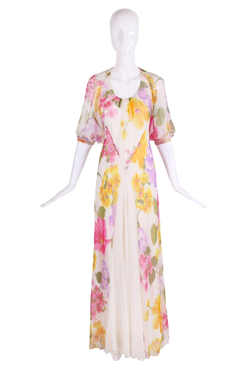 1970's Stavropoulos bias cut white silk chiffon evening gown with floral pattern in yellow, pink, purple, orange and green. Gown is made from a double layer of silk, has short sleeves with band and white panel at front. In excellent condition -