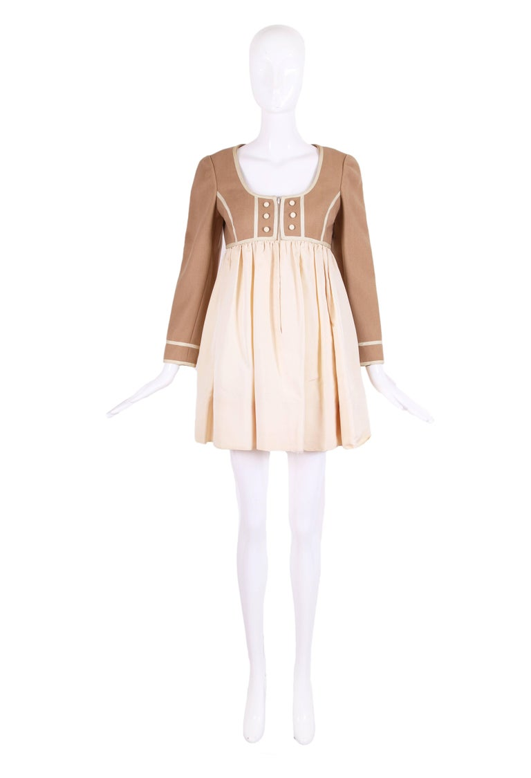 1960's classic Geoffrey Beene baby doll dress in contrast colored fabric at the top and bottom. The bodice top is made of camel colored wool and decorated with six faux fabric covered buttons and decorative piping at darts, waist, neckline and