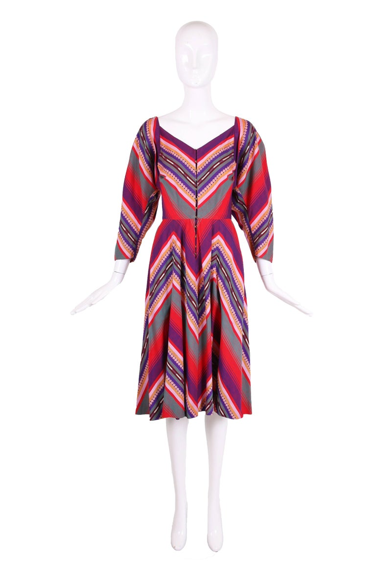 1950's Claire McCardell Clothes by Townley cotton serape print day dress in purple, red, pink, orange, navy blue, and green. Dress has a V-neck, dolman sleeves, and full skirt. Metal hook and eye closures down center front. Hidden pockets at both
