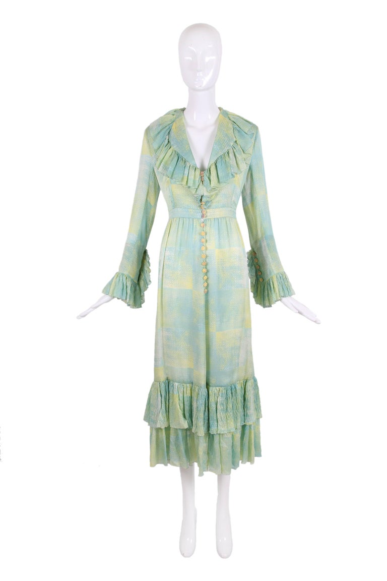 1970's Chloe silk abstract print dress in shades of pale green, blue and yellow, with a deep v-neckline and ruffle trim at collar, sleeve cuffs and tiered hem. Dress fastens up center front with yellow buttons and green fabric loopholes, with the