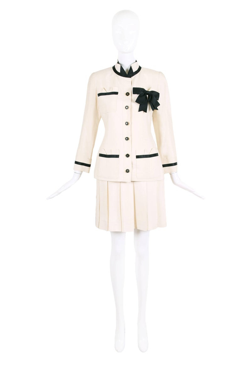 Vintage Chanel cream-colored silk shantung jacket and skirt set with black and gold CC logo button closure down center front of jacket. Jacket features a black silk band and black silk bow design motif - with black band trim at the four frontal