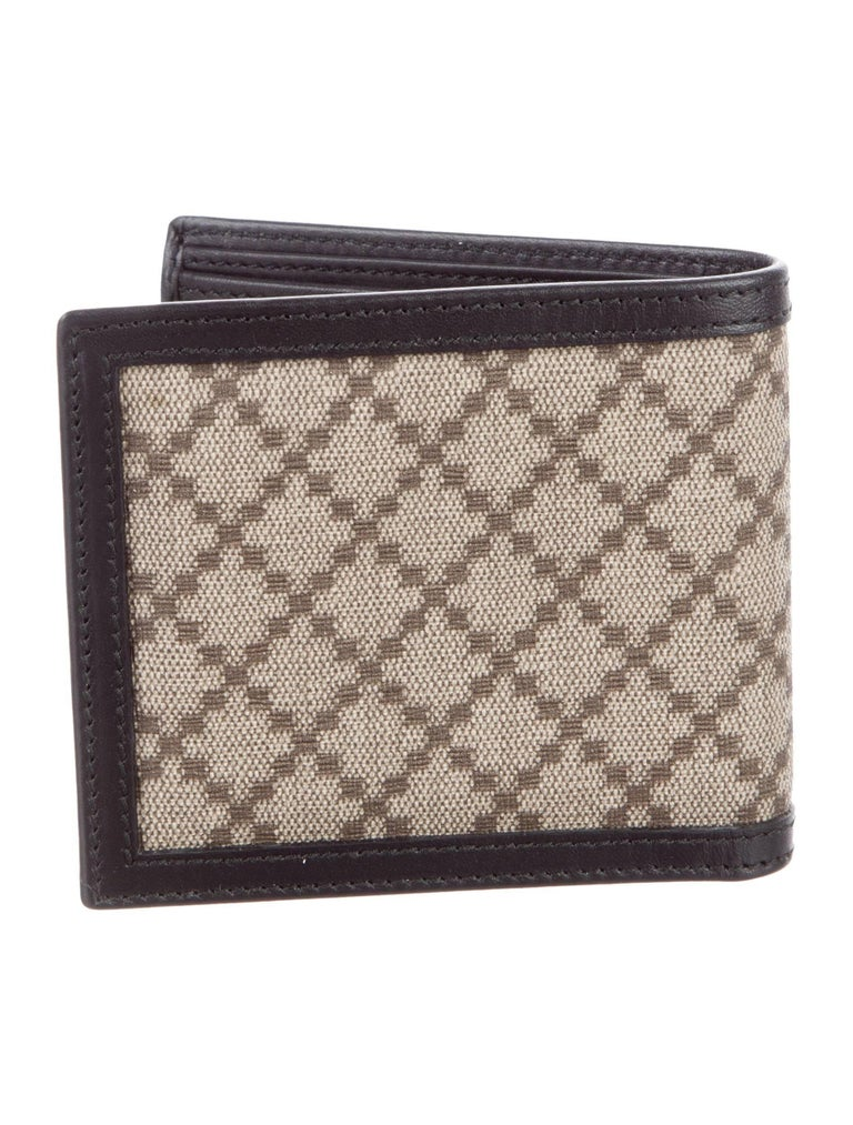 """Gucci New Monogram Canvas Leather Men's Bifold Suit Wallet in Box  Canvas Leather Made in Italy Features bill compartments and size card slots Measures 4"""" W x 3.75"""" H x 0.75"""" D Includes original Gucci box"""