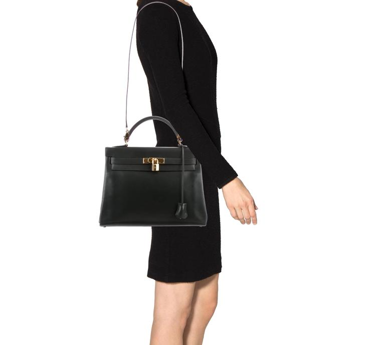 CURATOR'S NOTES  Hermes Kelly 32 Black Box Gold Satchel Shoulder Bag With Accessories available at Newfound Luxury   Two words: Status symbol. Hermes Retourne Kelly 32 with all original Hermes accessories.  A rare find of this age and