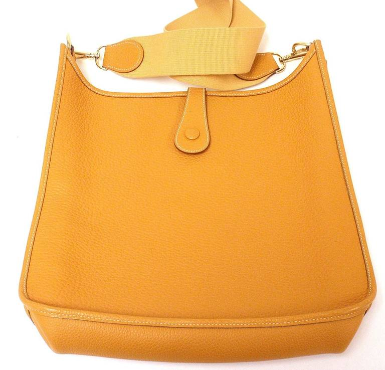 HERMES EVELYNE GM MUSTARD YELLOW CLEMENCE GHW SHOULDER BAG, 2002   This bag is in EXCELLENT condition. Features supple leather exterior with sueded leather interior.   Please note, color can vary greatly from monitor to monitor. This color can