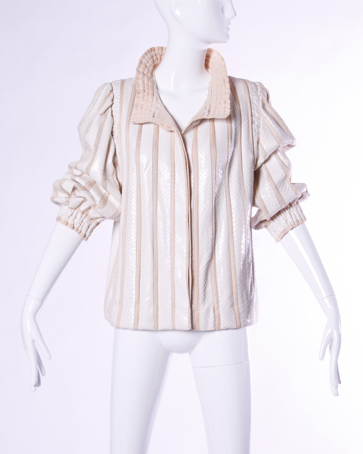 Vintage white reptile skin jacket with ribbed knit panels and full balloon sleeves. Ruffled collar and sleeve cuffs.  Details:  Fully Lined Side Pockets Shoulder Pads Sewn Into Lining Front Button Closure Color: Cream/ Beige Fabric: Reptile
