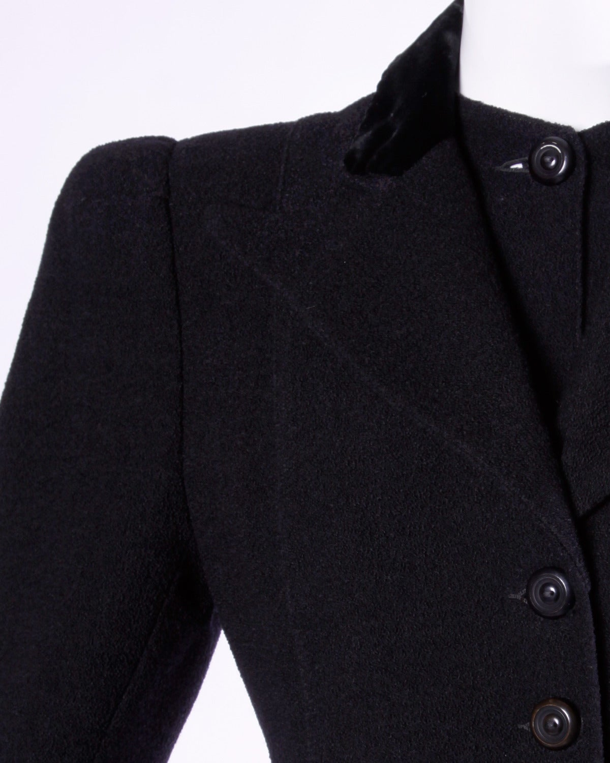 Gorgeous black wool tailored coat from the 1940s featuring bold shoulders and flared princess shape. Unique collar detail buttons under the lapels giving the appearance of a second piece.