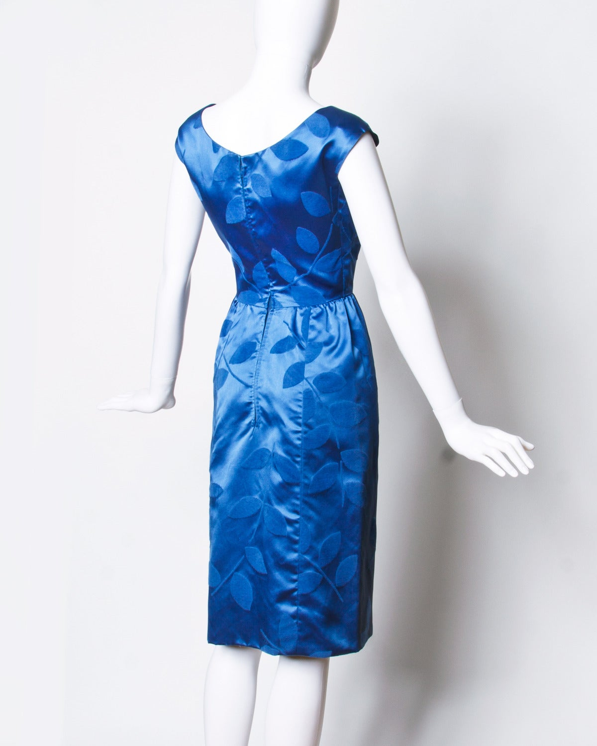 """Vintage blue silk satin cocktail dress with a tiny nipped waist and hourglass silhouette.  Details:  Fully Lined Back Metal Zip Closure Estimated Size: XS Color: Blue Fabric: Silk Satin  Measurements:  Bust: 34"""" Waist: 24"""" Hips:"""