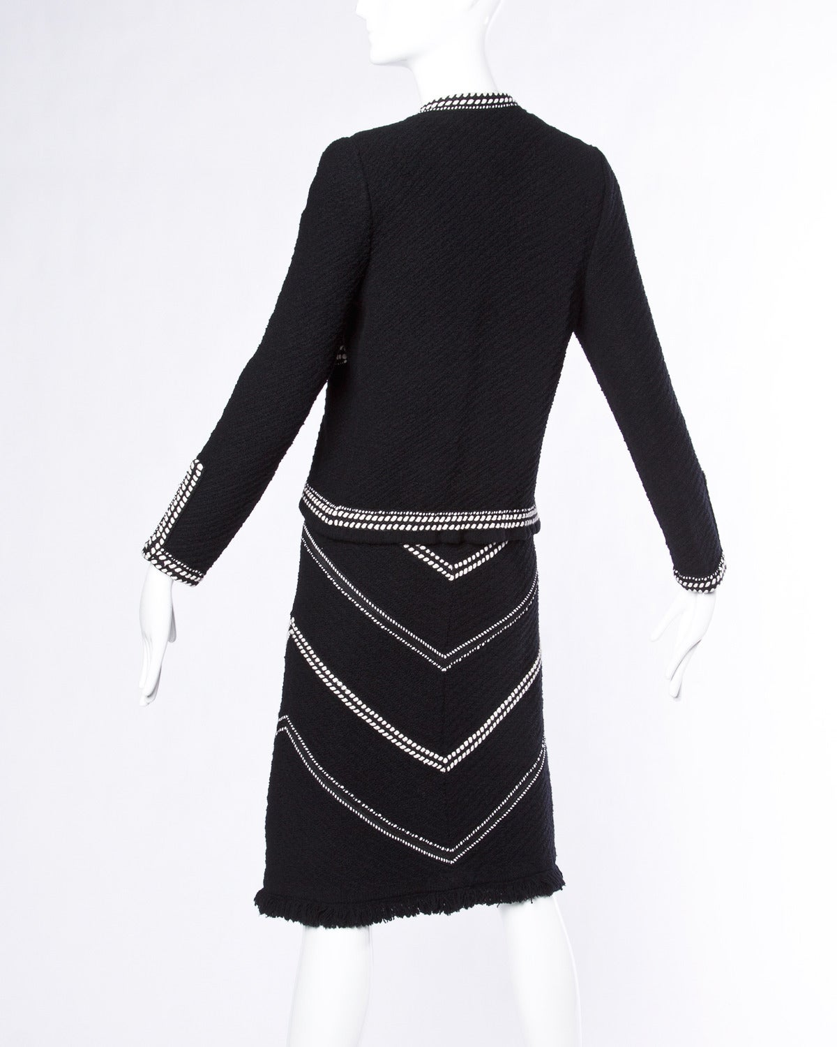 Two piece skirt suit in black and white boucle wool by Adolfo. Chevron stripes and fringe trim.  Details:  White Braid Trim 100% Wool Boucle Knit Open Front Jacket. Pull On Elastic Waist Pencil Skirt Label: Adolfo  Colors: Black /