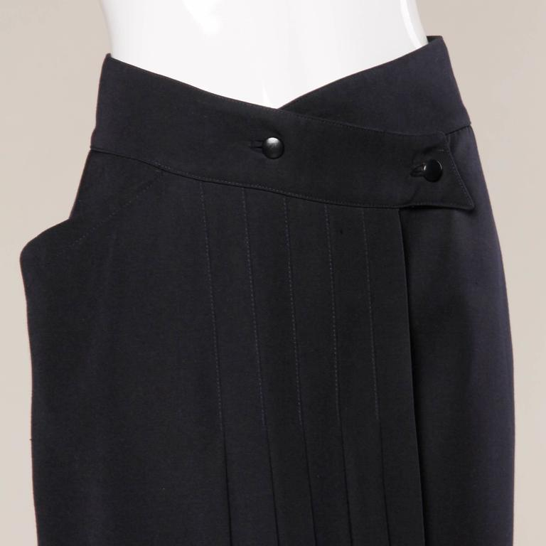 Gorgeous vintage navy blue wool avant garde skirt by Claude Montana. Unique cut with pleating and one side pocket. Fully lined with front button closure. The marked size is a US 6. The skirt fits true to the marked size. The measurements are as