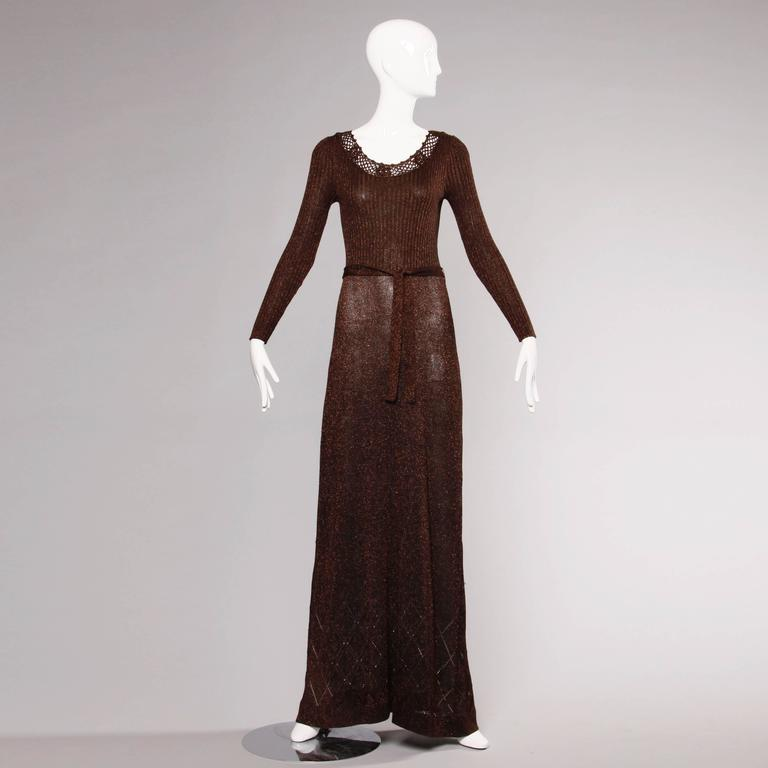 Metallic bronze knit maxi dress with crochet trim, long sleeves and a matching sash by Wenjilli. Unlined. Rear zip closure. 66% acrylic, 22% metallic, 12% polyester. Marked size 9/10, but fits like a modern size small-medium. The measurements are as