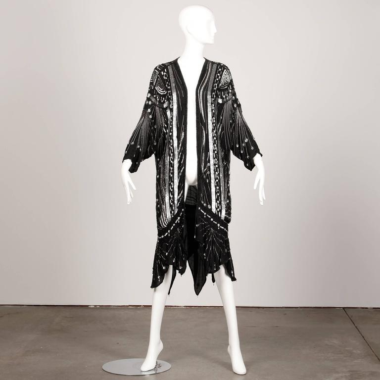 Sparkling Art Deco-inspired silk duster completely encrusted with thousands of sparkling sequins and beads. Scarf hem hits mid-calf. Fully lined in silk with front hook closure. This piece should fit most sizes on account of the oversized shape. The