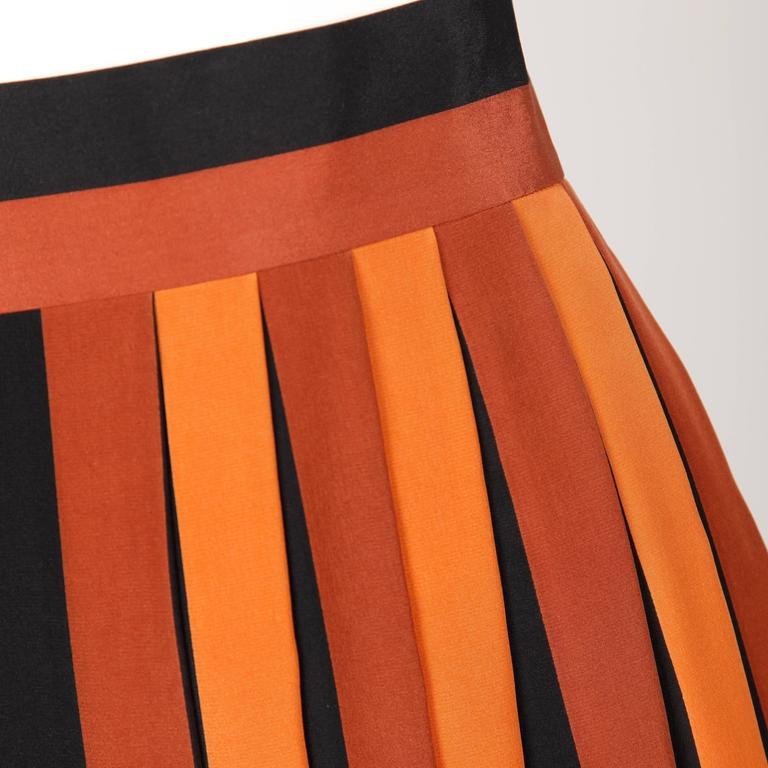 Wonderful 1970s silk pleated color block skirt by Givenchy. Rust, black, white, neutral and orange colors with inverted pleats and a striped waistband. Marked size 38, fits like a modern size small. 100% Silk. Unlined with zip and hook closure. Made