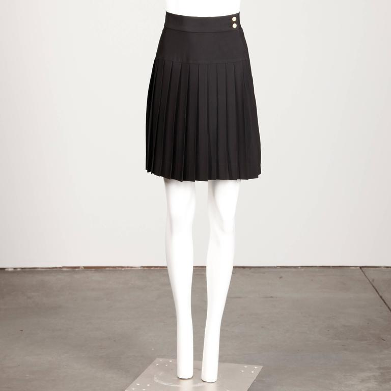 "Classic black pleated skirt by Karl Lagerfeld for Chanel. Asymmetric gold button and zip closure. Partially lined. 52% Acetate 48% Rayon. The marked size is 38 and the skirt fits like a modern size small. The waist measures 26"", hips 38"""