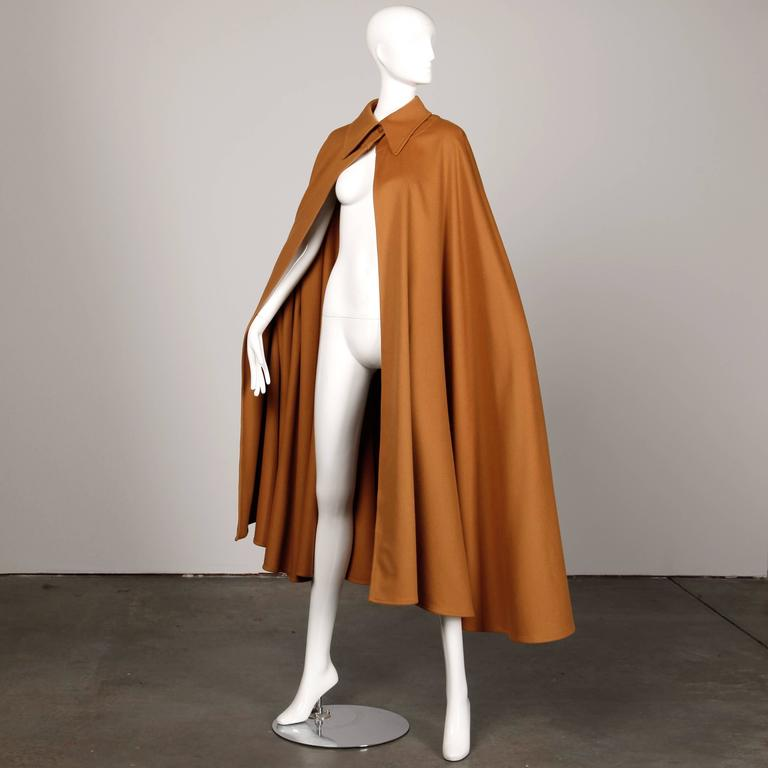 Incredible vintage heavy wool cape coat by Emanuel Ungaro from the 1970s. Single button closure at the front of the neck. Beautiful camel colored wool. Unlined. This cape should fit most size on account of its free shape. The total length measures