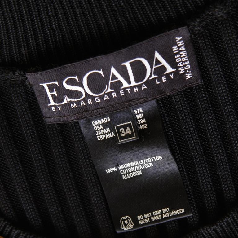 """Vintage black ribbed cotton knit top by Escada with shiny gold stud appliques. Short sleeves. Unlined. 100% Cotton. The marked size is an EU 34 and the top fits like a modern size small. The bust measures 30-40"""", waist 24-38"""", and total"""