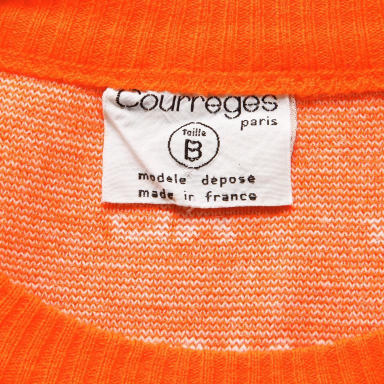 "Bright orange vintage Courreges sweater vest from the 1970s with the Courreges logo throughout the piece. Unlined. Pulls on. The bust measures 34-36"", waist 26-30"", and total length 20"". This piece fits like a modern size small and is"