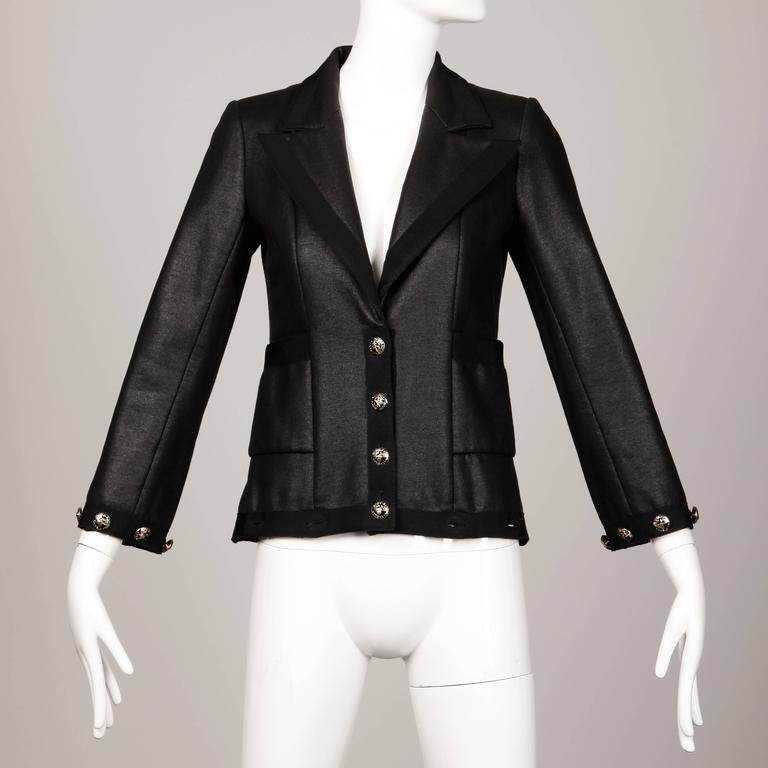 "Stunning black Chanel coat that converts to a jacket by buttoning off the bottom panel! From Chanel's 2008 ""Coco-Line"" Airline Cruise Collection. This coat/jacket features silver and black ""Coco-Line"" airplane novelty buttons and"
