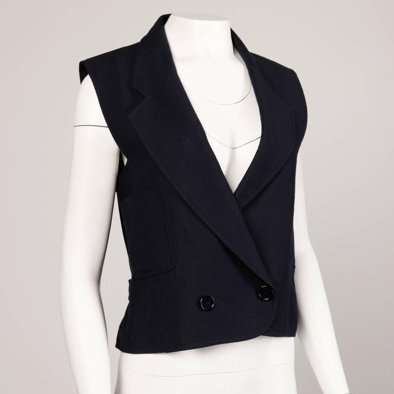 "Beautifully done navy blue wool vest by Bernard Perris with back buckle detail. Fully lined. Fits like a modern size small-medium. The bust measures 38"", waist 34"", and total length 22"". Excellent condition with no noted flaws."
