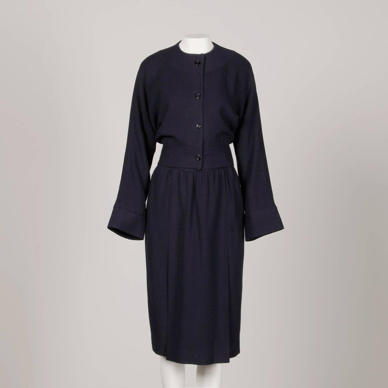 Elegant vintage 1970s navy blue wool jacket and skirt suit by Donald Brooks. The jacket is fully lined with front button and snap closure. Structured shoulder pads are sewn in underneath the lining. 100% wool. The marked size is 12. The bust