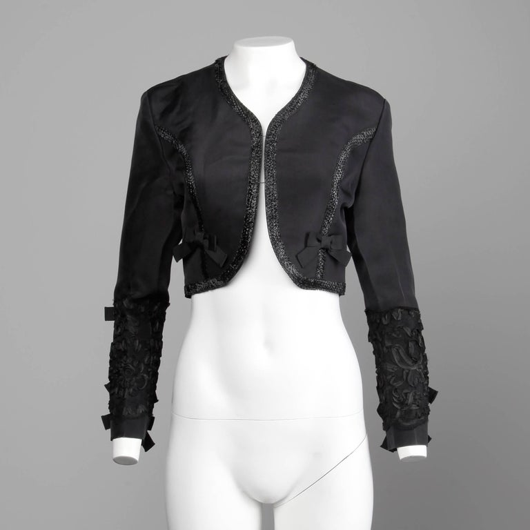 """Vintage 1990s black silk cropped jacket by Gemma Kahng with ribbon and bow detail. Fully lined with no closure. The marked size is 6, and the jacket fits like a modern small. 100% silk. The bust measures 40"""", waist 28"""", shoulders"""