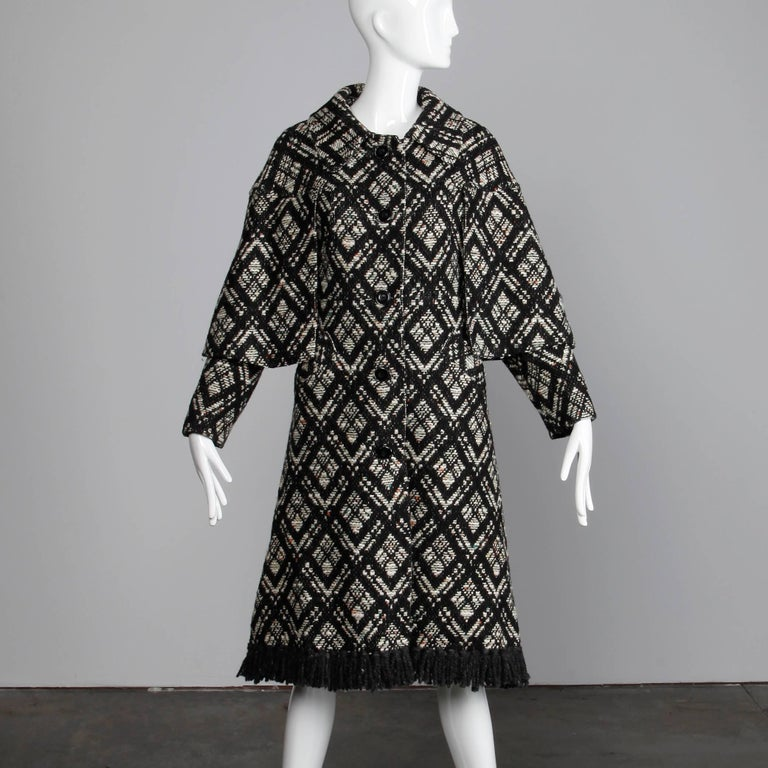 """Darling vintage 1970s black and white Irish wool coat with attached cape detail and black fringe trim. Fully lined with front button closure. Front pockets. Fits like a modern size small. The bust measures 36"""", waist 33"""", hips 41, drop"""