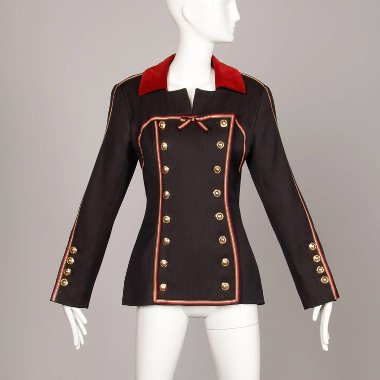 Incredible vintage Gemma Kahng! Military-inspired double breasted buttons, red velvet trim and striped ribbon detail. Fully lined with front button and snap closure. Faux rear pockets. Structured shoulder pads are sewn in underneath the lining. The